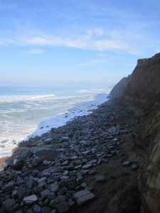 The Boulders Trying To Hold Back The Erosion. The Cliff You Can See Is Very Steep As Some Has Fallen Into The Ocean.