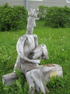 King Holding Baby Driftwood Sculpture In Sainte Anne des Monts.