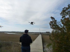 David Flying The Quadcopter Over The Fishing Pier And Marsh Land.
